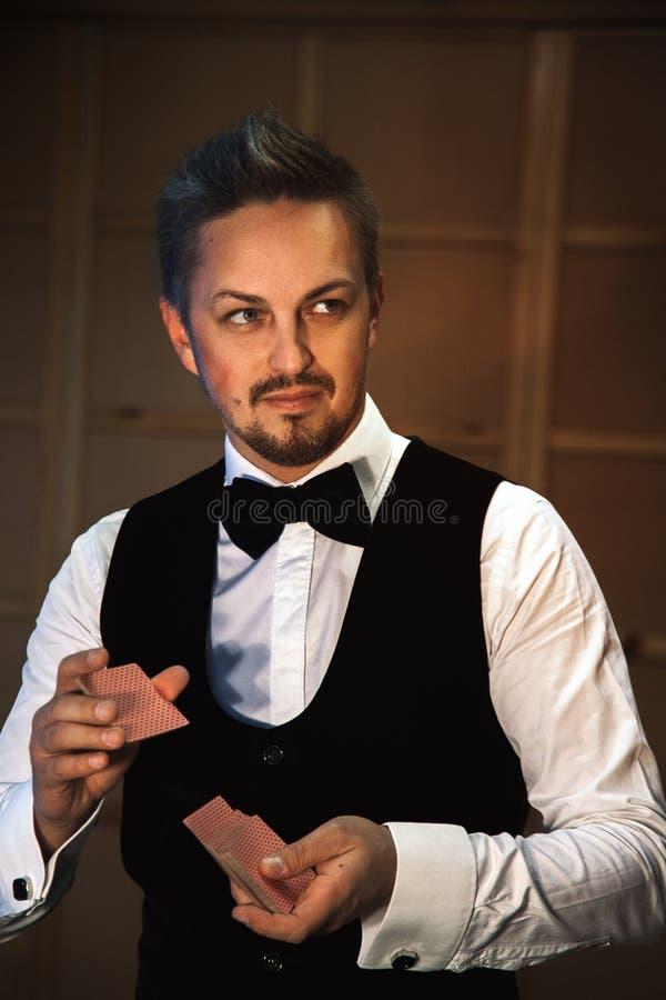 Gut aussehender Mann in einem weißen Hemd mit einer Fliege schlurft die Karten lizenzfreies stockbild