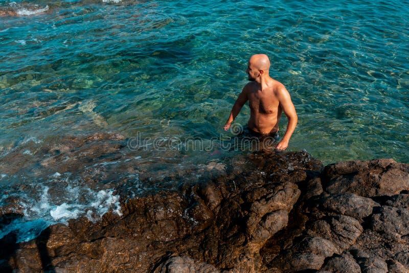 Gut aussehender Mann an einem wilden felsigen Strand lizenzfreie stockfotos
