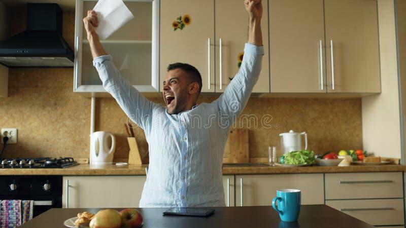 Gut aussehender Mann erhalten Brief der guten Nachrichten Lesein der Küche, während frühen Morgen des Frühstücks zu Hause haben S lizenzfreie stockbilder