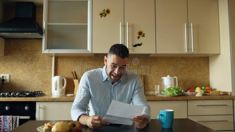 Gut aussehender Mann erhalten Brief der guten Nachrichten Lesein der Küche, während frühen Morgen des Frühstücks zu Hause haben S lizenzfreies stockfoto