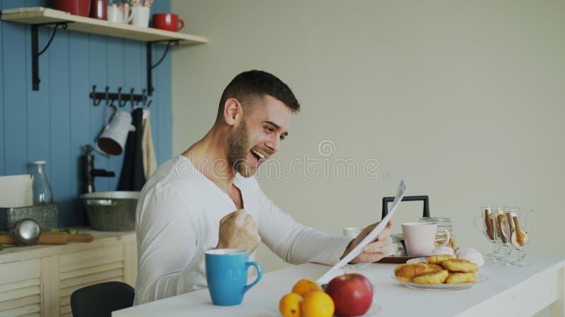 Gut aussehender Mann erhalten Brief der guten Nachrichten Lesein der Küche, während frühen Morgen des Frühstücks zu Hause haben S stockbilder