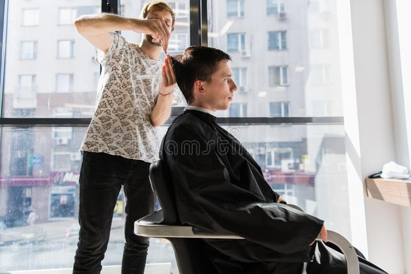 Gut aussehender Mann am Friseur, der einen neuen Haarschnitt erhält lizenzfreie stockbilder