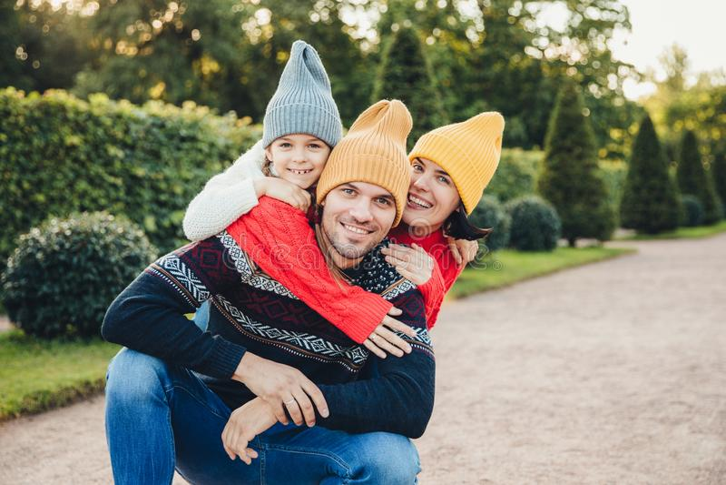 Gut aussehender Mann hat gutes Verhältnis zur Frau und kleine Tochter, die ihn von der Rückseite umfassen, haben angenehmes Läche stockfotografie