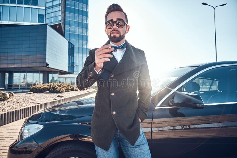 Gut aussehender Mann im Mantel steht nahe seinem Neuwagen beim Rauchen am Parken lizenzfreie stockfotografie