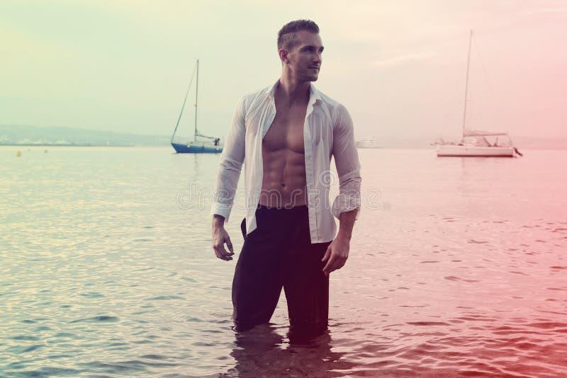 Gut aussehender Mann im Meer stockfotos