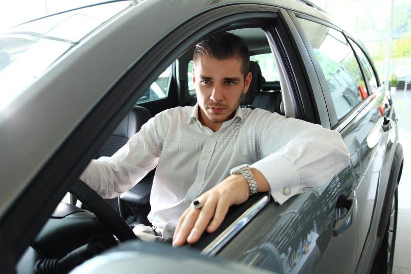 Gut aussehender Mann im Neuwagen lizenzfreie stockfotografie