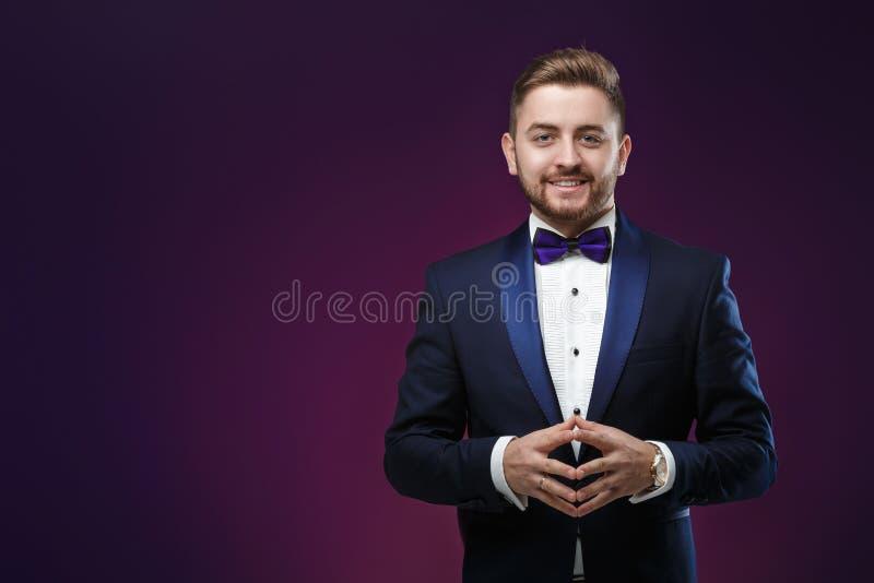 Gut aussehender Mann im Smoking und in Fliege, die Kamera betrachten Moderne, festliche Kleidung Zeremonienmeister auf dunklem Hi lizenzfreie stockbilder