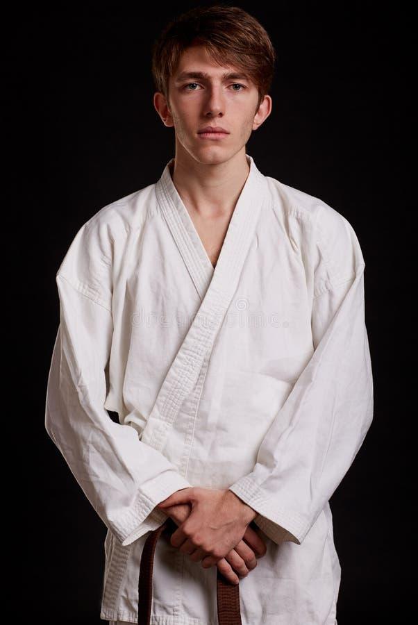 Gut aussehender Mann im weißen Kimono auf einem schwarzen Hintergrund Junge, der kämpfende Techniken lernt Karatelektionskonzept stockbilder