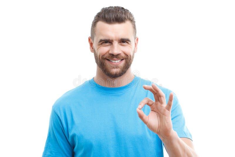 Gut aussehender Mann mit dem Bart, der o.k. darstellt lizenzfreie stockfotos