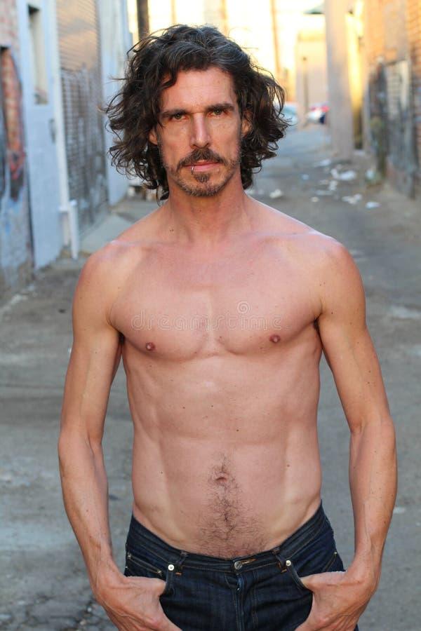 Gut aussehender Mann mit dem langem Haar und Bart Er wirft vor Kamera gerade mit offenen Jeans auf und zeigt seine Muskeln Abdomi stockfoto