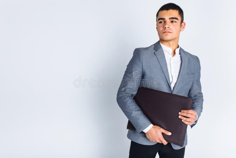 Gut aussehender Mann mit dem Ordnermann, der ein Menü, einen stilvollen Geschäftskerl in der Klage im Studio auf weißem Hintergru lizenzfreie stockfotos