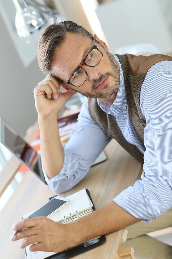 Gut aussehender Mann mit den Brillen, die im Büro arbeiten stockbild