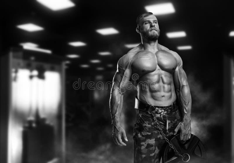 Gut aussehender Mann mit den großen Muskeln, werfend an der Kamera in der Turnhalle auf lizenzfreies stockbild
