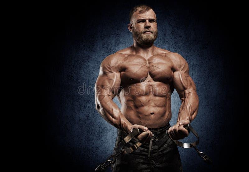Gut aussehender Mann mit den großen Muskeln, werfend an der Kamera in der Turnhalle auf stockfotos
