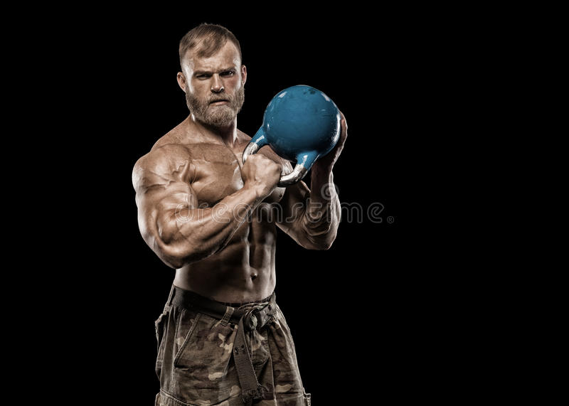Gut aussehender Mann mit den großen Muskeln, werfend an der Kamera in der Turnhalle auf stockbild