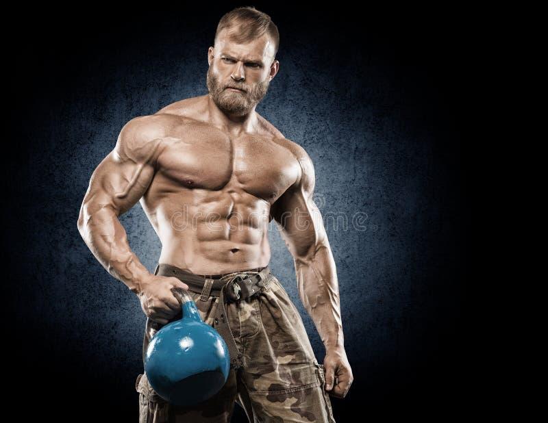 Gut aussehender Mann mit den großen Muskeln, werfend an der Kamera in der Turnhalle auf lizenzfreies stockfoto