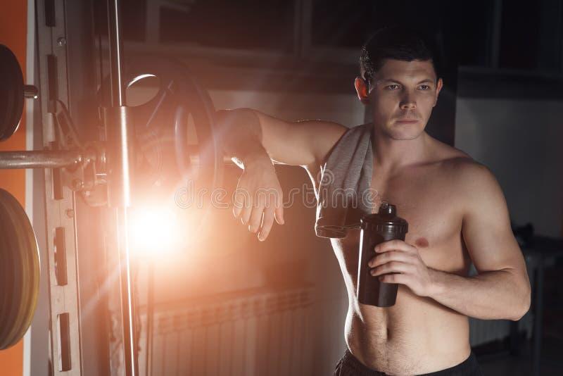 Gut aussehender Mann mit den großen Muskeln, werfend an der Kamera in der Turnhalle auf stockfoto
