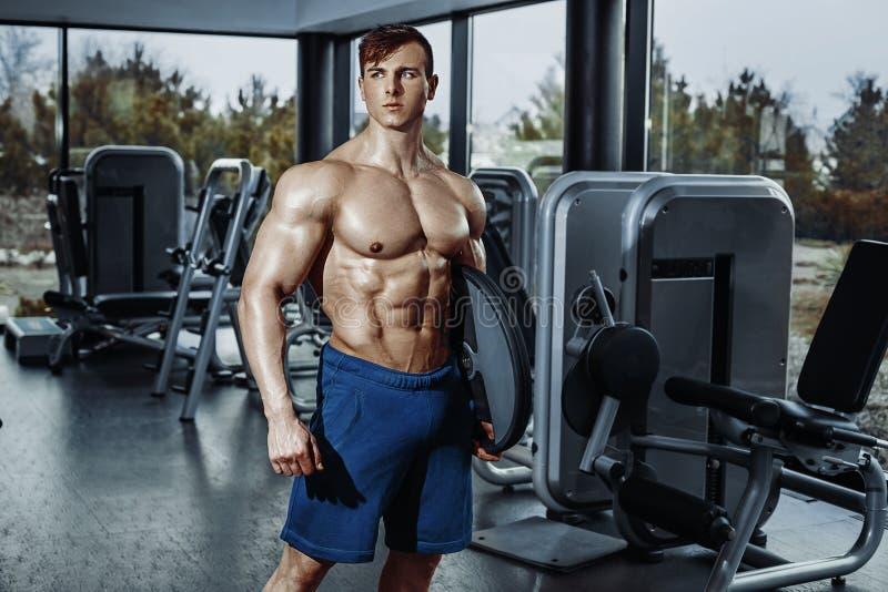 Gut aussehender Mann mit den großen Muskeln, werfend an der Kamera in der Turnhalle auf lizenzfreie stockbilder