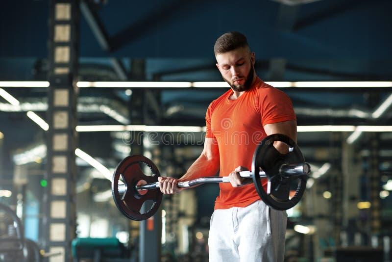 Gut aussehender Mann mit den gro?en Muskeln, werfend an der Kamera in der Turnhalle auf lizenzfreies stockbild