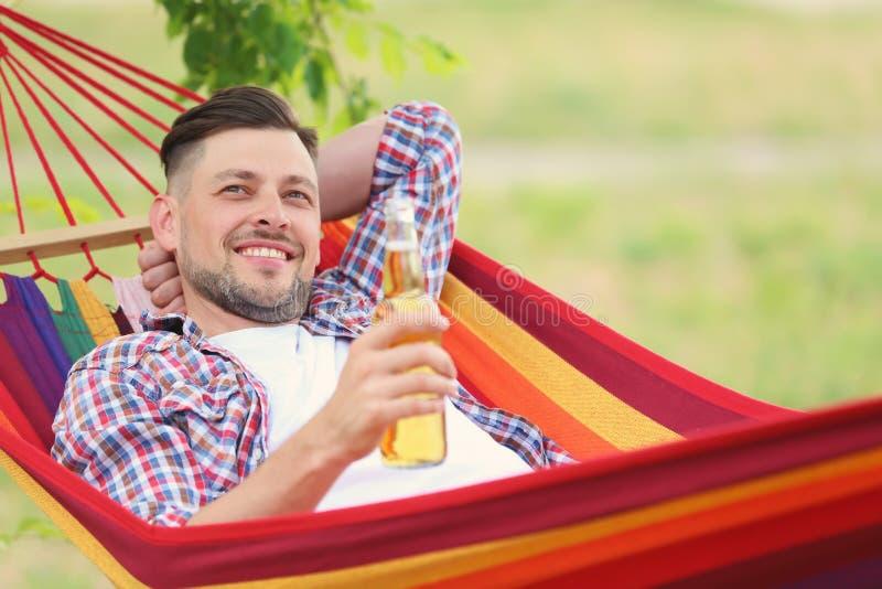 Gut aussehender Mann mit der Flasche Bier draußen stillstehend in der Hängematte lizenzfreie stockbilder