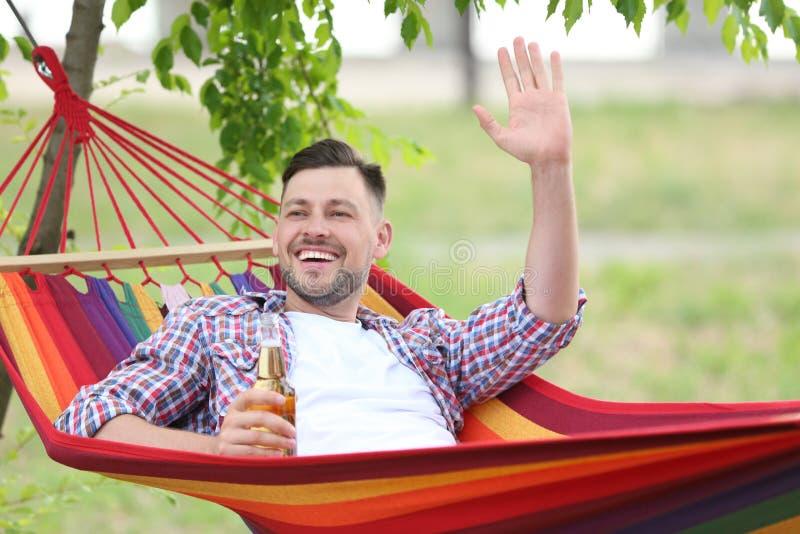 Gut aussehender Mann mit der Flasche Bier draußen stillstehend in der Hängematte lizenzfreies stockfoto