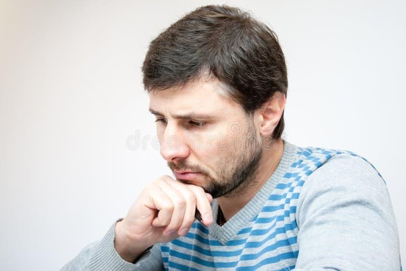 Gut aussehender Mann mit einem Stift in seinen Handblicken unten durchdacht stockfotografie
