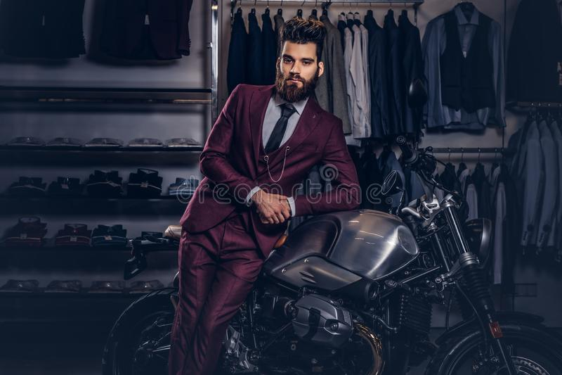 Gut aussehender Mann mit einem stilvollen Bart und einem Haar kleidete in der roten Klage der Weinlese an, die nahe Retro- Sportm lizenzfreie stockfotos