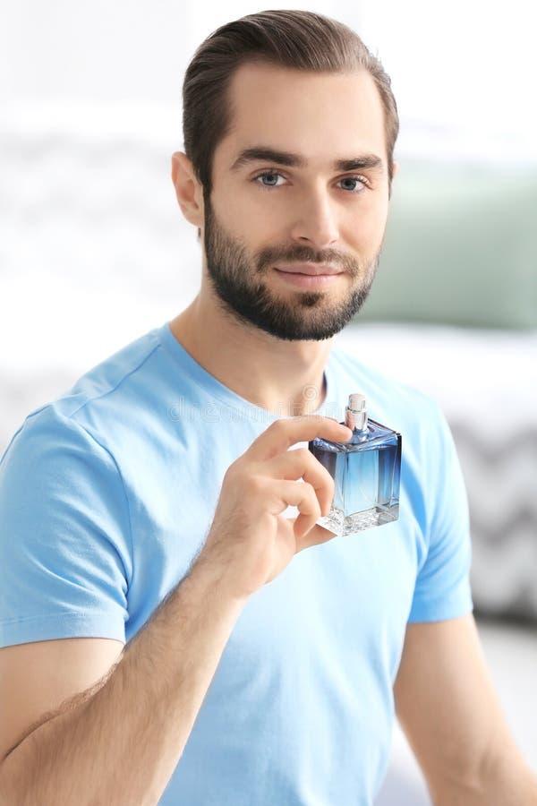 Gut aussehender Mann mit Flasche Parfüm stockfotos