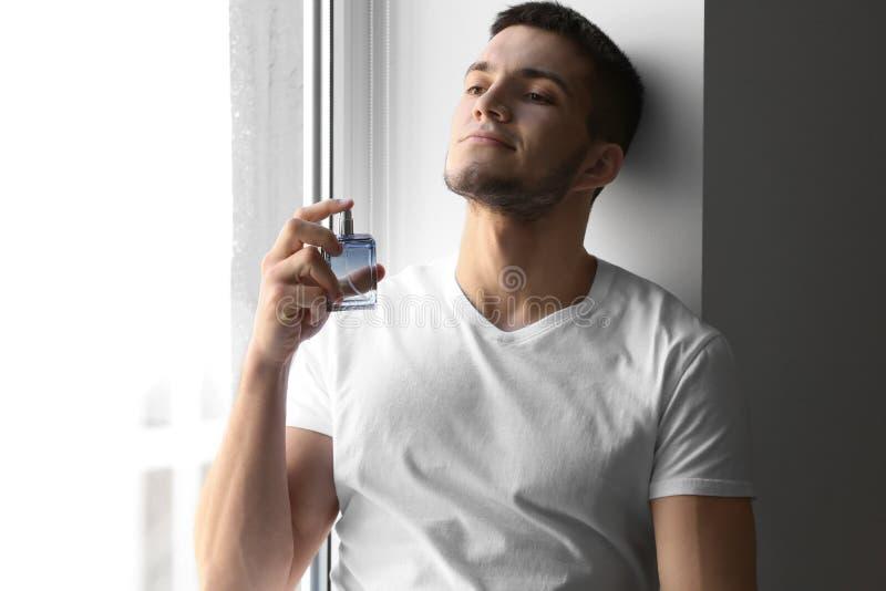 Gut aussehender Mann mit Flasche Parfüm stockbild