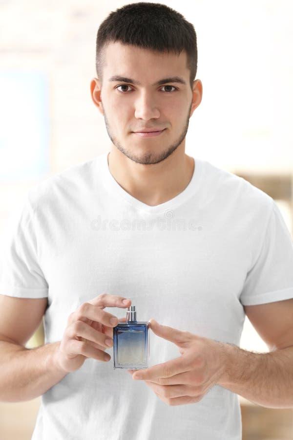 Gut aussehender Mann mit Flasche Parfüm lizenzfreies stockfoto