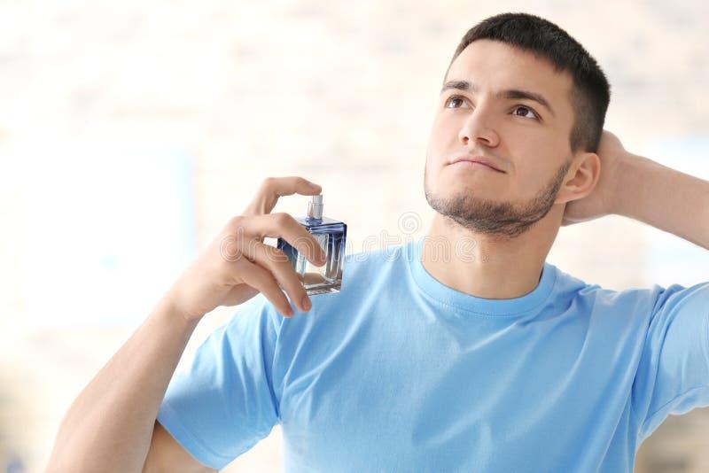 Gut aussehender Mann mit Flasche Parfüm lizenzfreie stockfotos
