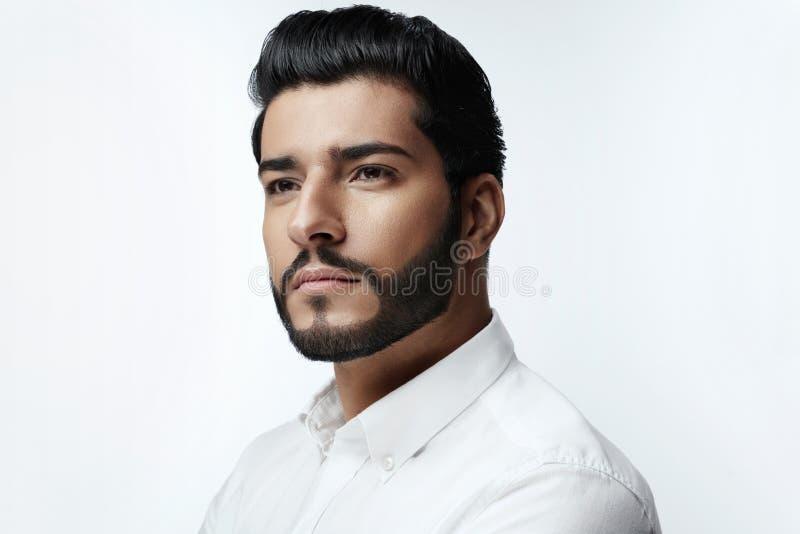 Gut aussehender Mann mit Frisur, Bart und Schönheits-Gesichts-Porträt stockbilder