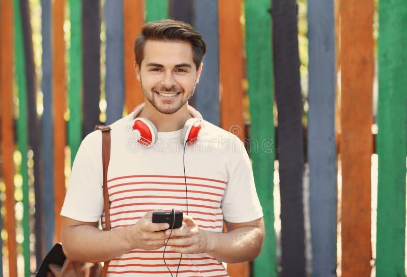 Gut aussehender Mann mit hörender Musik der Kopfhörer auf buntem Hintergrund lizenzfreies stockbild