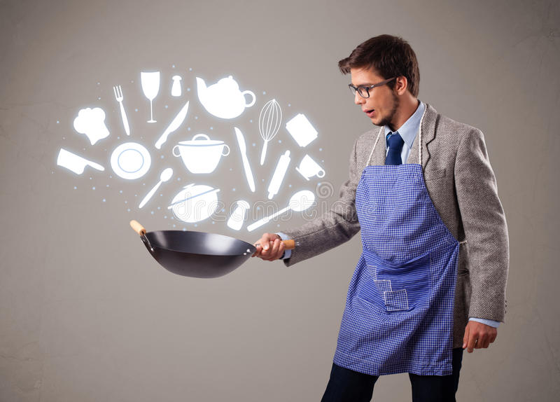 Gut aussehender Mann mit Küchenzubehörikonen stockbild