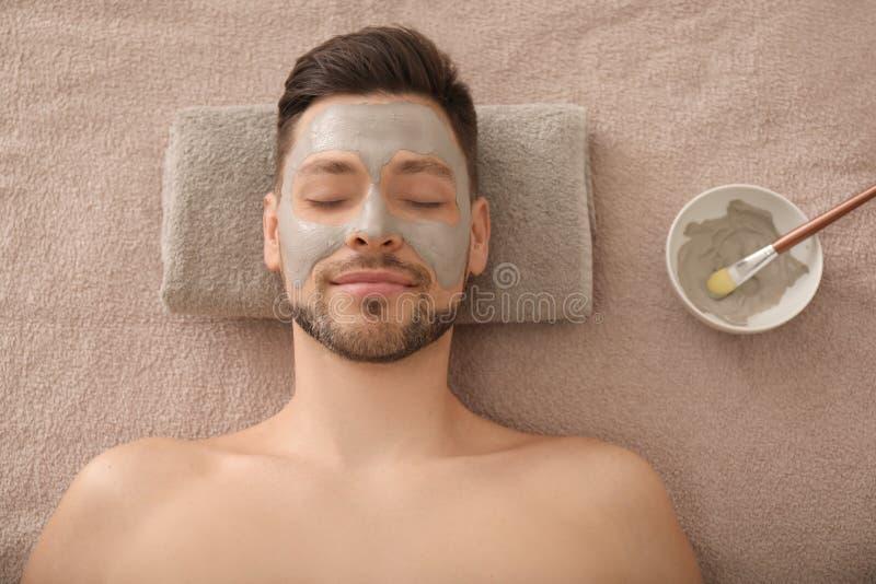 Gut aussehender Mann mit kosmetischer Maske im Badekurortsalon lizenzfreies stockfoto