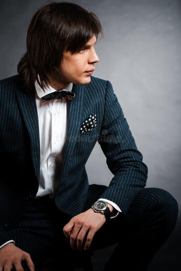 Gut aussehender Mann mit langem Haar Brunette und braune Augen im dunklen Anzug stockbilder