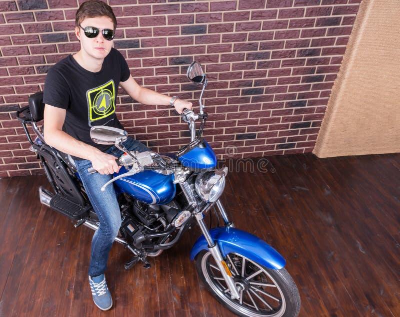 Gut aussehender Mann mit Schatten auf seinem Motorrad stockbild