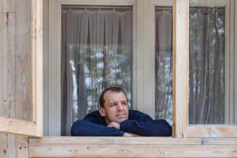 Gut aussehender Mann am offenen Fenster stockfoto
