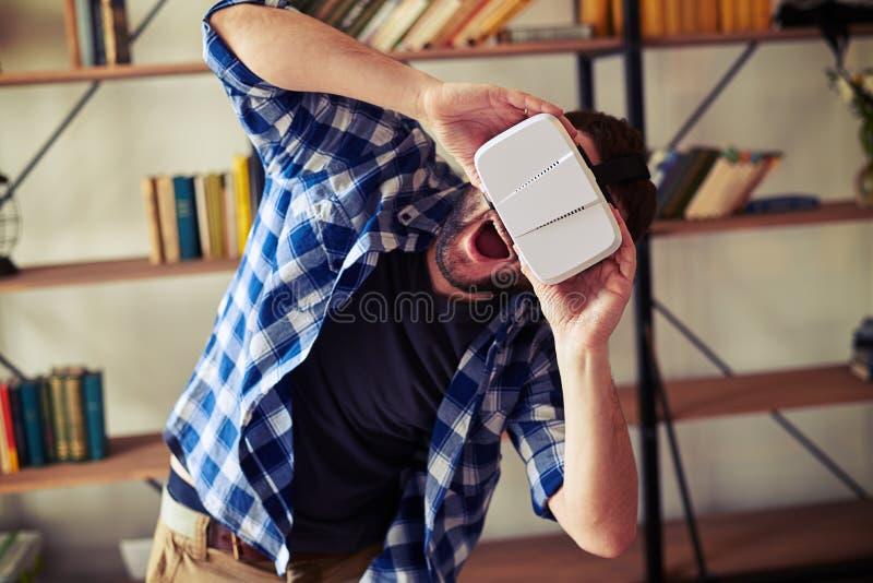 Gut aussehender Mann sehr aufgeregt unter Verwendung der Gläser der virtuellen Realität stockbilder