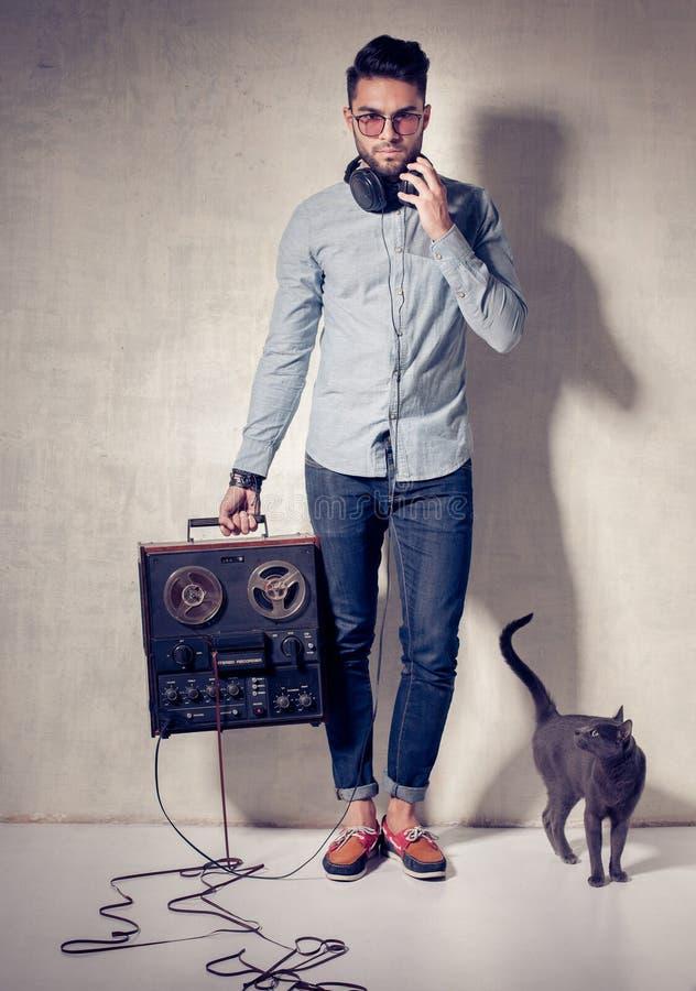 Gut aussehender Mann und Katze, die Musik auf einem magnetophone hören lizenzfreie stockbilder