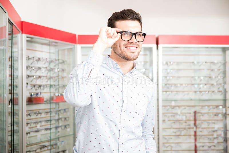 Gut aussehender Mann wählt Schauspielrahmen im optischen Salon lizenzfreies stockfoto
