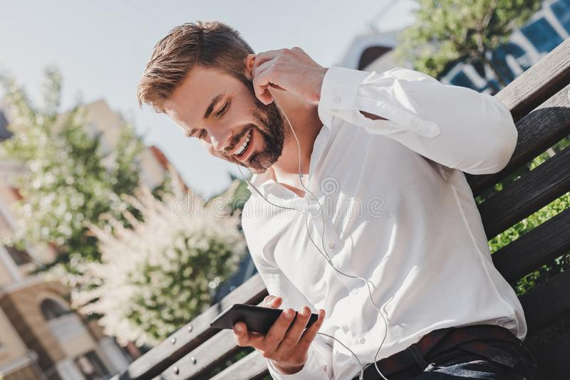 Gut aussehender Mann wird Telefonanruf unter Verwendung der Kopfhörer machen Er sitzt auf einer Bank im Park lizenzfreies stockbild