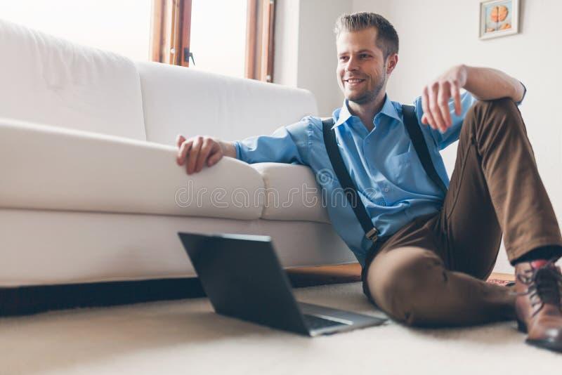 Gut aussehender Mann zu Hause unter Verwendung seines Laptops lizenzfreie stockfotografie