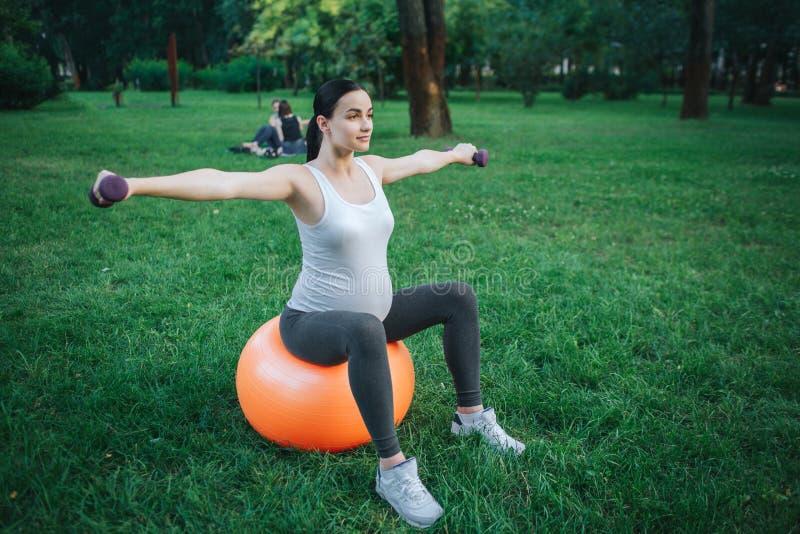 Gut gebaut junge schwangere Frau sitzen auf orange Eignungsball und dem Trainieren im Park Sie hält Dummköpfe lizenzfreie stockfotos