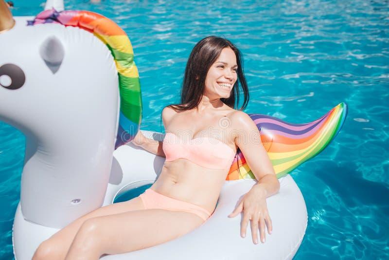 Gut gebaut Mädchen sitzt auf Luftmatraze und schaut Ti das Recht Sie trägt Pfirsichfarbschwimmenanzug Mädchen ist im Swimmingpool lizenzfreie stockfotos
