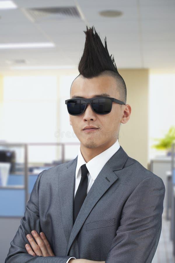 Gut gekleidet junger Mann mit Mohikaner und Sonnenbrille, Arme kreuzten im Büro stockbilder