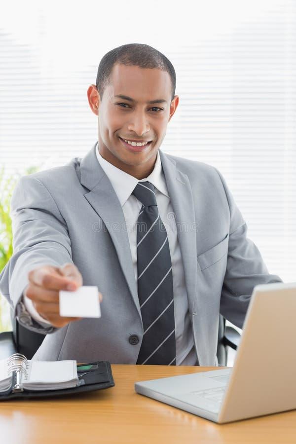 Gut gekleideter Mann, der Visitenkarte vor Laptop im Büro übergibt lizenzfreies stockbild