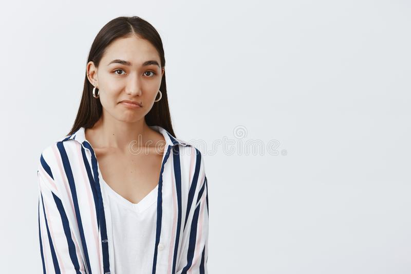 Gut habe ich Zweifel Ungewisser attraktiver und moderner weiblicher Mitarbeiter in gestreifter Bluse, in schürzender Lippe und im lizenzfreies stockfoto