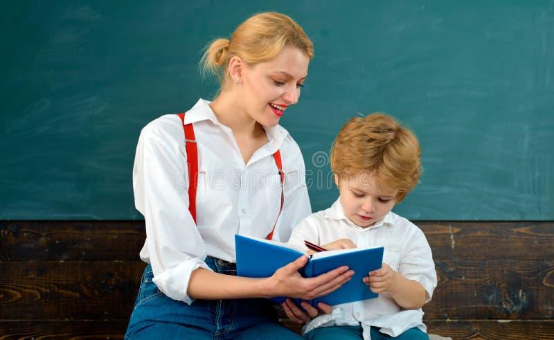 Gute Lehrerhilfsstudenten stellen gro?e Fragen B?cher Schule wieder Intelligente Pupille Kluger Junge Bester weiblicher Lehrer stockbilder