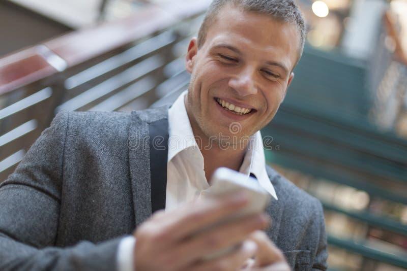 Gute Nachrichten! Männer, die sms auf smartphone im Geschäftsgebäude lesen lizenzfreie stockfotos